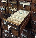 photo of drawers on a library card catalog with one drawer open
